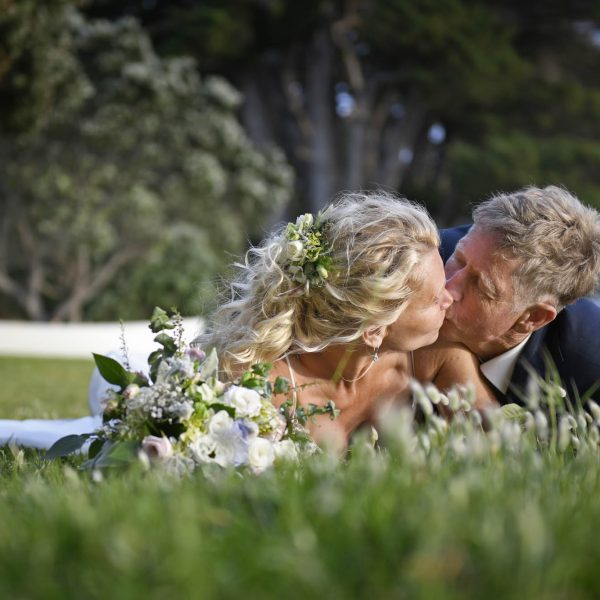 wedding portrait commercial photographers Wedding Photography beach Bride and Groom kissing in the grass